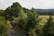 Stream cuts through the landscape as in the distance a farmer using a tractor gathers hay on the last day before rain is expected in his field in Reeth at Swaledale. Yorkshire, England, UK. This is a farming area where rural living and the countryside is at the centre of life in this county. Swaledale runs broadly from west to east. To the south and east of the ridge a number of smaller dales. Swaledale is a typical limestone Yorkshire dale, with its narrow valley-bottom road, green meadows and fellside fields, white sheep and dry stone walls on the glacier-formed valley sides, and darker moorland skyline.