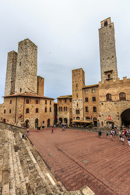 The Piazza del Duomo  in San Gimignano in Tuscany, Italy. Known as the Town of Fine Towers, San Gimignano is famous for its medieval architecture, unique in preserving about a dozen of its tower houses, which, with its hilltop setting and encircling walls, form an unforgettable skyline.