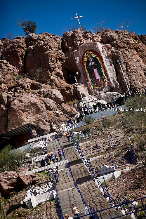 """SHOT 1/31/10 1:57:04 PM - The Virgin Mary painted high atop a hillside near Ciudad Obregon, Mexico along Highway 15. The site is a popular destination to leave well wishes and thanks by family members. The Virgin of Guadalupe has symbolized the Mexican nation since Mexico's War of Independence. Our Lady of Guadalupe (Spanish: Nuestra Señora de Guadalupe) is a celebrated Catholic icon of the Virgin Mary also known as the Virgin of Guadalupe (Spanish: Virgen de Guadalupe). The Lady of Guadalupe is of significant importance to Mexican Catholics and has been given the titles of """"Queen of Mexico"""", """"Empress of the Americas"""", and """"Patroness of the Americas"""". Roadside capillas, or tiny chapels, in the Mexican states of Nayarit, Sinaloa and Sonora. The capillas are common along the roads and highways of Mexico which is heavily Catholic and are often dedicated to certain patron saints or to the memory of a loved one that has passed away. Often times they contain prayer candles, pictures, personal artifacts or notes. (Photo by Marc Piscotty / © 2010)"""