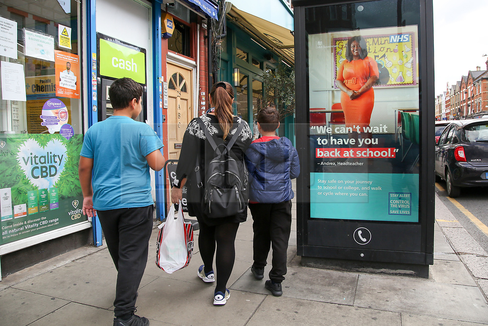 © Licensed to London News Pictures. 26/08/2020. London, UK. A woman and her children walk past 'We can't wait to have you back to school.' digital advert in north London, which is a part of the government's new public information campaign requesting children to return to school following the summer holidays, as the COVID-19 lockdown is eased. <br /> <br /> ***Permission Granted***<br /> <br /> Photo credit: Dinendra Haria/LNP