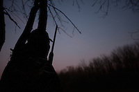 duck hunter leaning against a tree silhouetted