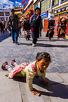 A Tibetan girl prostrating himself repeatedly as he circumambulates through Barkhor Square and along The Barkhor (around the area of the Jokhang Temple), the most sacred temple in Tibet, Lhasa, Tibet, China.