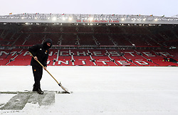 Ground Staff remove snow on the pitch before the Emirates FA Cup, quarter final match at Old Trafford, Manchester