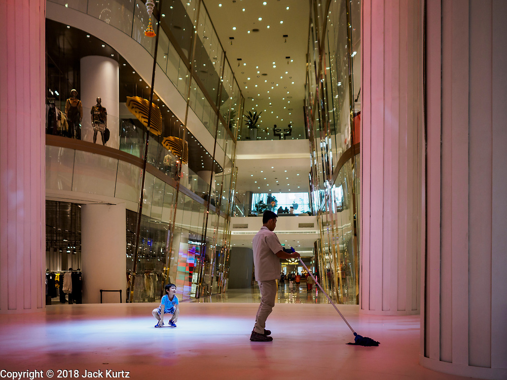 17 NOVEMBER 2018 - BANGKOK, THAILAND: A maintenance worker cleans in the ICONSIAM mall while a child plays nears him. ICONSIAM is a mixed-use development on the Thonburi side of the Chao Phraya River. It includes two large malls, with more than 520,000 square meters of retail space, an amusement park, two residential towers and a riverside park. It is the first large scale high end development on the Thonburi side of the river and will feature the first Apple Store in Thailand and the first Takashimaya department store in Thailand.      PHOTO BY JACK KURTZ