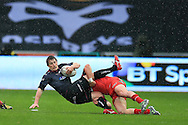 Jeff Hassler of the Ospreys is tackled by DTH Van Der Merwe of the Scarlets. Guinness Pro12 rugby match, Ospreys v Scarlets at the Liberty Stadium in Swansea, South Wales on Saturday 26th March 2016.<br /> pic by  Andrew Orchard, Andrew Orchard sports photography.