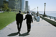 2 businessmen walking on a city waterfront
