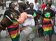 Rally in central London held by MDC every Saturday to protest against Robert Mugabe and his regime in Zimbabwe. Women drumming and dancing with baby in back carrier sling.