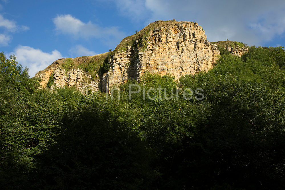 Sandstone cliffs at Sutton Bank, also known as Roulston Scar, is a hill in the Hambleton District of the North York Moors National Park, North Yorkshire in England, UK. It is a high point on the Hambleton Hills with extensive views over the Vale of York and the Vale of Mowbray.