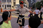 A British soldier with the Scottish British Black Watch Regiment keeps the public safely away from a vehicle leaving the Prince of Wales Barracks, on the eve of the handover of sovereignty from Britain to China, on 30th June 1997, in Hong Kong, China. Midnight signified the end of British rule, and the transfer of legal and financial authority back to China. Hong Kong was once known as 'fragrant harbour' (or Heung Keung) because of the smell of transported sandal wood.