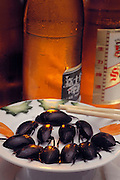Stir-fried black water beetles prepared for a restaurant meal in Guangzhou, China (cold beer in background). Image from the book project Man Eating Bugs: The Art and Science of Eating Insects.