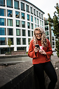 Woman texting on her smart device stood outside the International Finance Centre in the corporate and banking area of St Helier, Jersey, CI