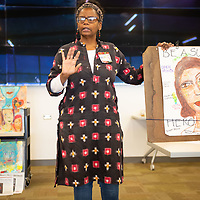 """NM State American Association of University Women (AAUW) Chair Marie Johnson, shares her art work and the meaning of the one on the table to the class during the """"Diversity: Where Are Our Heros?"""" lecture held at the UNM-Gallup campus on Tuesday in Gallup."""