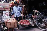 Vietnamese woman carrying some fruits with her yoke in a street of Hanoi