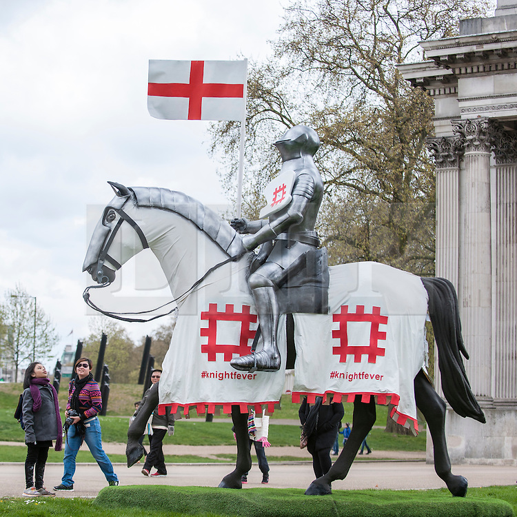 © Licensed to London News Pictures. 22/04/2015. Wellington Arch, London. Tourists walk by as English Heritage unveil a 15ft St George at Wellington Arch in honour of the Patron Saint ahead of England's largest St George's Day celebration at Wrest Park as well as the launch of a nationwide tour which will see the knight open jousting tournaments at castles across England. Photo credit : Stephen Chung/LNP