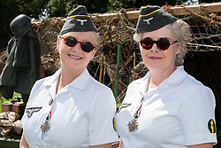 Female re-enactors portraying Wehrmacht Heferinnen with the German Army in Summer uniform. They are wearing the War Merit Cross with Swords, above is the Blitz pin or brooch and on the right sleeve is the Blitz badge worn by women trained in Army communications procedures. The brooch combined with the Yellow piping (waffenfarbe) on her hat would indicate they are a Nachrichtenhelferin (Signals Assistants with the German Army) Wehrmacht Heferinnen were the German Armed Forces female Auxiliaries. At various periods o time during world war two they were sometimes classified as military personnel other times as uniformed civilians employed by the German Armed Forces (Wehrmacht). Wearing medal on the uniform indicates it was presented that day under normal circumstances only the medal ribbon would be worn by the recpiant