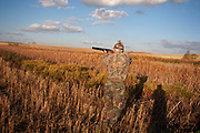 Experienced hunter Timmy Stein out on the North Dakota prariie grasslands, shooting upland game birds such as grouse near Minot, North Dakota, United States. Timmy has been shooting for most of his life and puts considerable efforts into his hunting, efforts which reward him with wild game meats, none of which is wasted. Here he uses an over and under up and under double barrel shot gun.