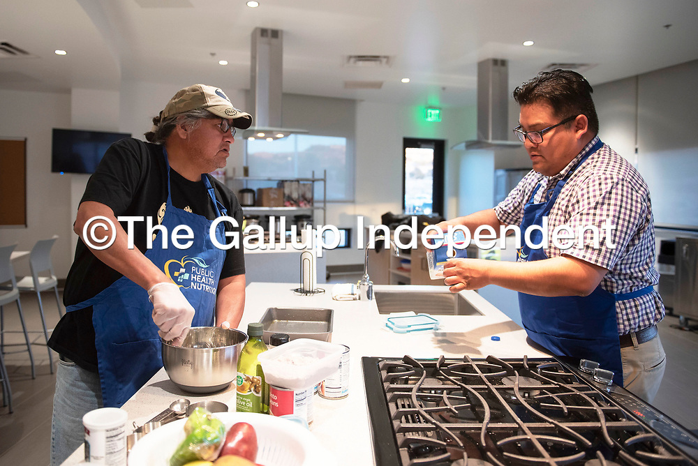 Danny John, left, begins preparing blue corn bread while Bronson Chee, nutrition outreach supervisor, helps measure out ingredients Wednesday night at Nihi Dine'é Bá Wellness Center during a men's cooking workshop hosted by Public Health Nutrition in Fort Defiance, Arizona.