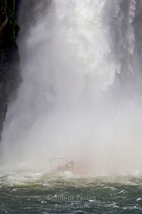 A tour boat with tourists passes under a large waterfall at Iguazu Falls. Iguazu Falls straddle the border between Argentina and Brazil.