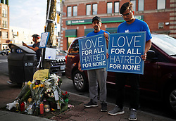 People hold signs at a memorial remembering the victims of a shooting on Sunday evening on Danforth, Ave. in Toronto, ON, Canada, on Monday, July 23, 2018. Photo by Mark Blinch/CP/ABACAPRESS.COM