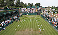 Spectators watch a match on court 18 on day three of the Wimbledon Championships at the All England Lawn Tennis and Croquet Club, Wimbledon.
