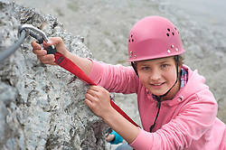Portrait girl climbing fixing carabiner to rope