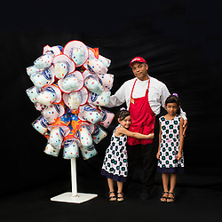 """Portrait of concession worker Milciades Jiminez with his daughters Allison and Alina.<br /> <br /> """"The best is you got your family together and we can work together. For example, my wife does the face-painting and I'm the one making the cotton candy. You know, the color candy made is by the sugar, with three different flavor, like pink, lemon and blue. It's three color. Kids always like candy. For some reason, kids always like candy. It's the most popular. And I'm the one making those candy happy. My wife does the face-painting. She's the one making people happy with the face. And my other girl helping me to make the candy to sell to the customer."""" <br /> <br /> After 146 years, the """"Greatest Show on Earth"""" will close its curtain in the end of May. <br /> Ringling Bros. and Barnum & Bailey Circus started in 1919 when the circus created by James Anthony Bailey and P. T. Barnum merged with the Ringling Brothers Circus. The circus' parent company, Feld Entertainment, made the decision to end the show after waning ticket sales and long court battles over the treatment of animals, particularly the elephants, made the costly entertainment event unsustainable."""