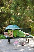A lady asleep in a garden bench holding an umbrella.