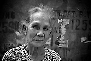 Portrait of an old woman in Hanoi, in front of a wall with phone numbers written on it.
