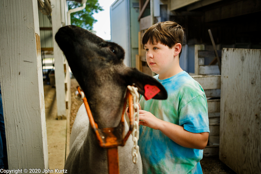 16 JULY 2020 - BOONE, IOWA: LEVI VENARD, 10, with one of his sheep on the first day of the Boone County Fair in Boone. Summer is county fair season in Iowa. Most of Iowa's 99 counties host their county fairs before the Iowa State Fair. In 2020, because of the COVID-19 (Coronavirus) pandemic, many county fairs were cancelled, and most of the other county fairs were scaled back to concentrate on 4H livestock judging. Boone county scaled back its fair this year. The Iowa State Fair was cancelled completely. Boone County Emergency Management did not approve going ahead with the fair, and has advised anyone who goes to the fair to take precautions and monitor themselves for symptoms of the Coronavirus.            PHOTO BY JACK KURTZ