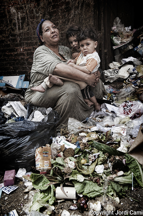 """A woman outside her home hugging his grandchildren during a break in the work of separation of organic waste from other garbage collected. On the outskirts of Cairo in the middle of Manshiet Nasr neighborhood is located Mokattam settlement known as """"Garbage City"""" is inhabited by Zabbaleen, a community of about 45,000 Coptic Christians living for decades to recycle waste generated by the Egyptian capital: plastic, aluminum, paper and organic waste transformed into compost. Most part of the Association for the Protection of the Environment (APE), an NGO that works in the area, whose objectives are to protect the environment and improve the livelihoods of garbage scavengers in Cairo. According to the UN, the work is done in Mokattam is one of the ten best examples of world environmental improvement. El Cairo , Egy<br /> pt, June 2011. ( Photo by  Jordi Camí )."""