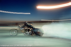 Nuclear Burn Out, Sturgis, South Dakota, 1988<br /> <br /> Limited Edition Print from an edition of 50. Photo ©1988 Michael Lichter.<br /> <br /> The Story: Being at the track is otherworldly.  I get in close as the tires burn out, the crack of the throttle exceeds what my eardrums can withstand and the rear tire pelts molten rubber all over me and my lenses. The nitro-methane makes me choke and my eyes flood with tears.  Add to this the hundred-degree temperatures and strong sun burning my skin. We love it and that's why we keep going back for more.