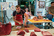 Stallholder fishmonger cutting tuna fish steaks at the Capo street market for fresh food in Palermo, Sicily, Italy