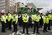 Metropolitan Police officers form a cordon around a bus used by Extinction Rebellion activists to block a road junction to the south of London Bridge on the ninth day of their Impossible Rebellion protests on 31st August 2021 in London, United Kingdom. Extinction Rebellion are calling on the UK government to cease all new fossil fuel investment with immediate effect.