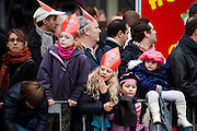 Children waiting for Saint Nicolas at  Sinterklaas parade, Dam Square, Amsterdam, 14th November 2010. Sinterklaas, the basis for Santa Claus in other countries, arrives from Spain by boat,  accompanied by Black Peter, played by multitudes of white Dutch people in blackface - a tradition that evokes some controversy. Contrary to traditions of Santa Claus elsewhere, Sinterklass arrives by boat, then rides through the streets on his grey horse, Amerigo,  in mid-November, bringing in the Christmas season. The Zwarte Pieten (Black Peters) distribute sweets and gingerbread cookies to the crowd along the parade route.
