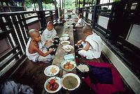 September 1987, Mandalay, Burma (Myanmar) --- Apprentice monks eat their lunch at a monastery in Mandalay, Burma. --- Image by © Owen Franken/CORBIS