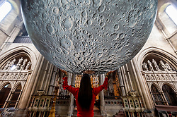 © Licensed to London News Pictures. 19/08/2021. LONDON, UK.  A woman poses with Luke Jerram 's Museum of the Moon, a 7m diameter artwork featuring detailed NASA imagery of the lunar surface.  At an approximate 1:500,000 scale, each centimetre of the internally lit sphere represents 5km of the moon's surface. The touring artwork is on display until 30 August at St John the Baptist Church near Shepherd's Bush and forms part of this year's Kensington and Chelsea Festival.  Photo credit: Stephen Chung/LNP