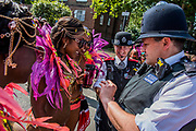 Police help Dancers with a plaster as they prepare for the parade - The Monday of the Notting Hill Carnival. The annual event on the streets of the Royal Borough of Kensington and Chelsea, over the August bank holiday weekend. It is led by members of the British West Indian community, and attracts around one million people annually, making it one of the world's largest street festivals.