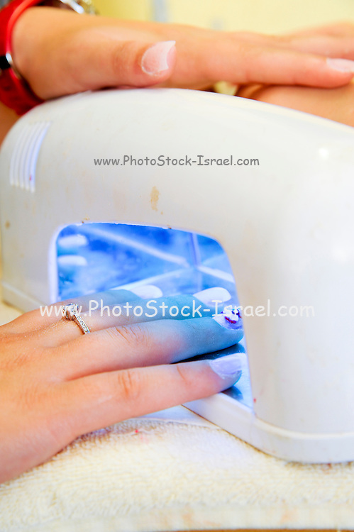 Woman receiving manicure, drying the nail polish