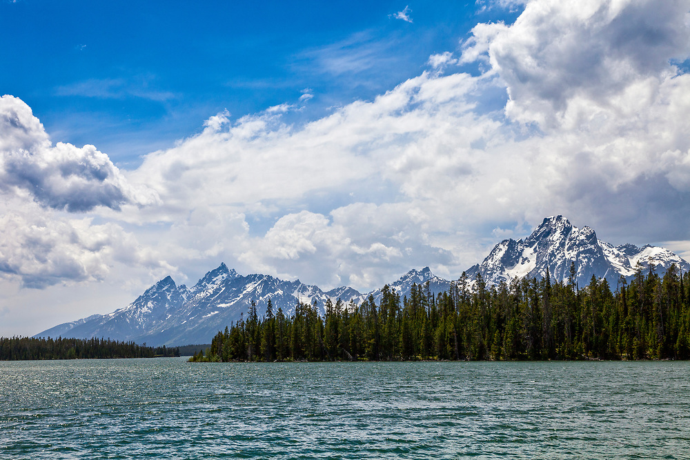 Waters edge view of Jackson Lake and the Teton Mountain Range in Teton National Forest on beautiful calm spring morning from Colter Bay. Licensing and Open Editions