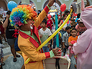 09 JANUARY 2016 - BANGKOK, THAILAND:        A clown blows up balloons during Children's Day festivities at Government House. National Children's Day falls on the second Saturday of the year. Thai government agencies sponsor child friendly events and the military usually opens army bases to children, who come to play on tanks and artillery pieces. This year Thai Prime Minister General Prayuth Chan-ocha, hosted several events at Government House, the Prime Minister's office.       PHOTO BY JACK KURTZ
