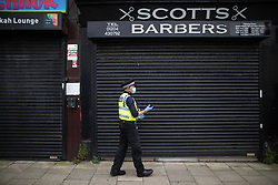 © Licensed to London News Pictures . 11/09/2020. Bolton , UK . PC TONY LOWE outside a shuttered Scott's Barber Shop . EHOs Caroline Greenen and Leanne Richardson are shut inside the premises by a member of staff after they issue a direction order to close Scott's Barber Shop in Horwich for a minimum of seven days  , with immediate effect , pending a review of the business . Police officers from Greater Manchester Police and Environmental Health Officers from Bolton Council respond to concerns of breaches of Coronavirus regulations , as stricter lockdown measures and a curfew on hospitality businesses are imposed in the borough to limit the spread of Covid-19 . Photo credit : Joel Goodman/LNP