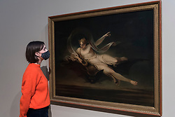 """© Licensed to London News Pictures. 15/10/2020. LONDON, UK.  London, UK. 15 October 2020. A staff member views """"Arial on a Bat's Back"""", 1819, by Henry Singleton. The work is part of new displays in Tate Britain's three collection routes: Rothko and Turner (a new route to celebrate 50 years since Mark Rothko first gave Tate his iconic Seagram Murals to join paintings he so admired by JMW Turner), British Art 1540-1920 and British Art 1930-Now.  Visitors may book online for free to visit the museum.  Photo credit: Stephen Chung/LNP"""