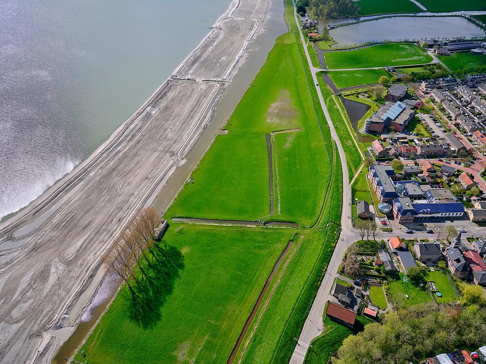 Nederland, Noord-Holland, gemeente Koggenland; 07-05-2021; Hoogheemraadschap Hollands Noorderkwartier, Scharwoude met het dijkmagazijn aan de IJsselmeerdijk, rood pannendak, zwart geteerd. In het kader van de dijkverbetering wordt er een oeverdijk aangelegd, de nieuwe halfhoge dijk heeft een buitentalud wat voor de bestaande dijk aangebracht wordt. <br /> The Hollands Noorderkwartier water board, Scharwoude with the dike warehouse on the IJsselmeerdijk, red tiled roof, black tarred. As part of the dyke improvement, an embankment dyke is being constructed, the new half-height dyke has an outer slope which will be installed in front of the existing dyke.<br /> <br /> luchtfoto (toeslag op standard tarieven);<br /> aerial photo (additional fee required)<br /> copyright © 2021 foto/photo Siebe Swart