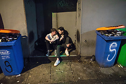 """© Licensed to London News Pictures . 17/12/2016 . Manchester , UK . Two men sit in a doorway in an alleyway off Peter Street . Revellers out in Manchester City Centre overnight during """" Mad Friday """" , named for being one of the busiest nights of the year for the emergency services in the UK . Photo credit : Joel Goodman/LNP"""