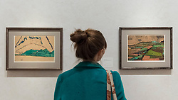 """© Licensed to London News Pictures. 31/10/2018. LONDON, UK. A visitor views (L to R) """"Carinthian Landscape"""", 1914, and """"Field Landscape (Kreuzberg near Krumau)"""", 1910, by Egon Schiele. Preview of """"Klimt / Schiele:  Drawings from the Albertina Museum,Vienna"""" exhibition at the Royal Academy.  Over 100 works on paper are on display in an exhibition which marks the centenary of the deaths of the two most celebrated and pioneering figures of early twentieth-century art.  The show runs 4 November to 3 February 2019.  Photo credit: Stephen Chung/LNP"""