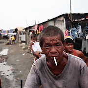 A man smokes a cigarette while walking through the Baseco area of Tondo on October 9, 2008 in Manila, the Philippines. Photo Tim Clayton
