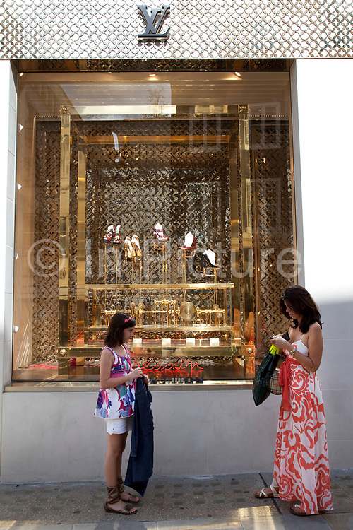 """Mother and daughter outside Louis Vuitton. Exclusive shops on New Bond Street, Mayfair, central London. It is one of the principal streets in the West End shopping district and is more upmarket. It has been a fashionable shopping street since the 18th century. Technically """"Bond Street"""" does not exist: The southern section is known as Old Bond Street, and the northern section, which is rather more than half the total length, is known as New Bond Street. The rich and wealthy shop here mostly for high end fashion and jewellery."""
