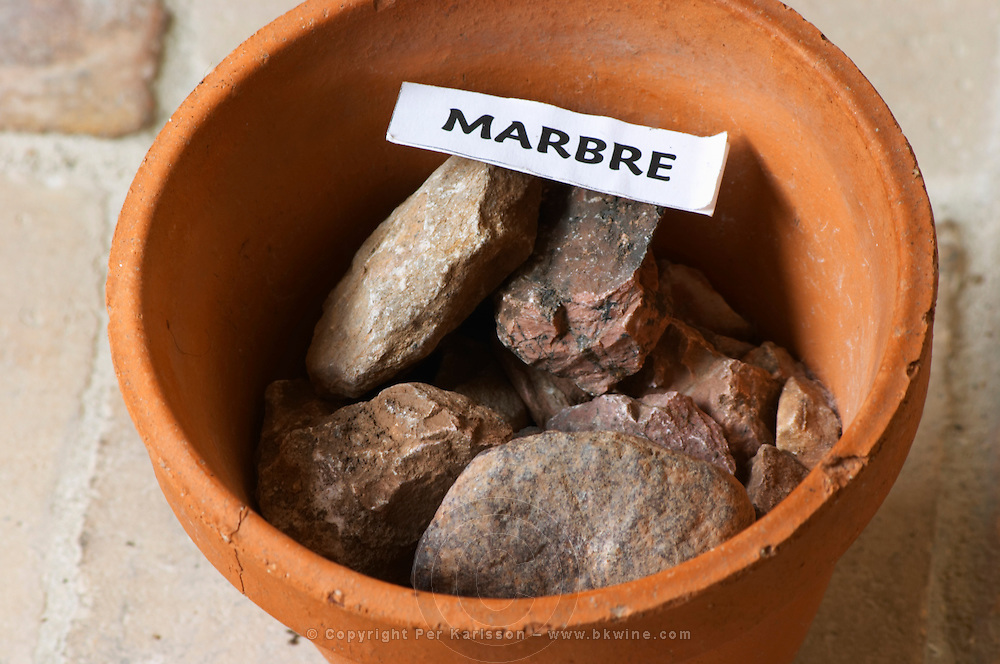 Plant pot with soil sample to illustrate different soil types, part of a series: marble rock, marbre. Chateau Villerambert-Julien near Caunes-Minervois. Minervois. Languedoc. Terroir soil. France. Europe. Soil with stones rocks.
