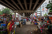 People shopping at a street market that takes place under a highway in the Tejgaon railway district on the 23rd of September 2018 in Dhaka, Bangladesh.