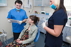 Dentist in consultation with patient; while dental nurse looks on,